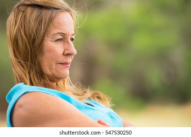 Portrait profile attractive mature woman, sad, thoughtful, depressed, sitting lonely outdoor, blurred background, copy space.