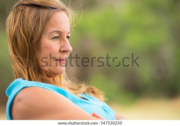 Porträtprofil attraktive reife Frau, traurig, nachdenklich, deprimiert, sitzend einsam draußen, unscharfer Hintergrund, Kopienraum.