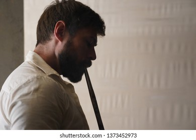 Portrait in profile of a brutal bearded man with short brown hair in a white creased shirt on a white blurred background. Handsome male smokes a hookah and inhales smoke through a wooden mouthpiece.
