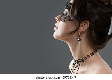 Portrait in profile of sensual girls in lace mask and bare shoulders posing in studio