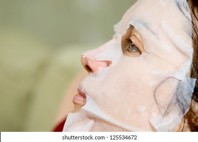 Portrait in Profile woman applying rejuvenating facial mask on her face.