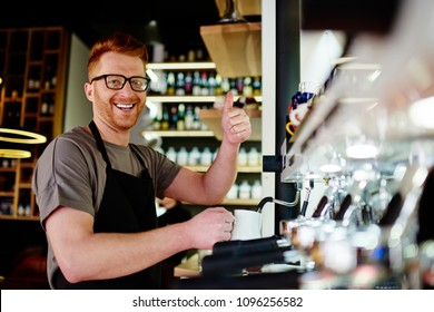 Portrait of prosperous young man working professional barista smiling at camera with finger up while preparing coffee beverage for client on modern machine.Positive male waiter showing sign ok