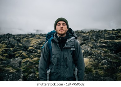 Portrait of proud and brave young adventurer hiker, explorer handsome man with trekking backpack stand on rocky hiking trail or path, look into camera. Outdoor vibes and adventures wanderlust