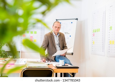 Portrait of proud businessman holding blueprint while sitting on conference table