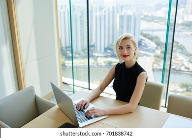 Portrait of proud female CEO working online checking financial report via laptop computer satisfied  with company income,charming businesswoman in formal elegant dress doing remote job in good mood
