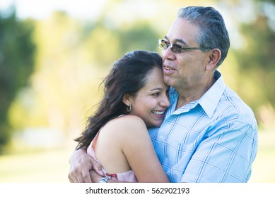 Portrait proud hispanic father cuddling happy relaxed smiling attractive adult daughter outdoor, blurred background.
