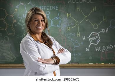 Portrait of a proud Hispanic teacher in front of a chalkboard in a classroom setting