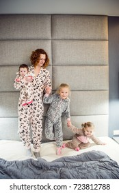 Portrait of a proud loving mother and happy little girl daughter sisters.Children wearing pajama.Laughing and having fun playing at home.Concept of love and happiness happy family.Family portrait.