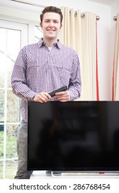 Portrait Of Proud Man With New Television At Home