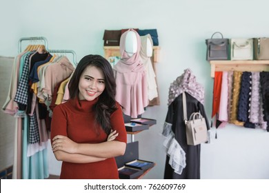 portrait of proud small fashion store owner smiling in her shop