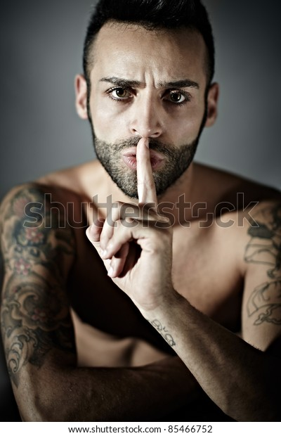 portrait of proud young adult man with tattoos hissing. Vertical shape, front view, studio shot