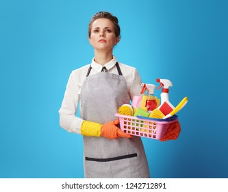 Portrait of proud young cleaning woman in apron with a basket with detergents and brushes isolated on blue. How to be competitive in the cleaning business? Just provide high quality cleaning services