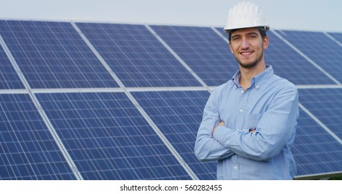 The portrait of a proud young engineer smiles satisfied with his successful work with his arms crossed. Concept: renewable energy, technology, electricity, service, green power.