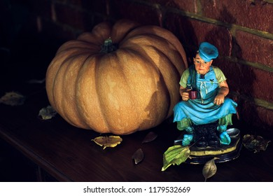 Portrait of a pumpkin next to a statue of a man drinking wine. Concept: holloween, horror, dark, scary