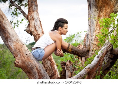 Portrait of punk girl sitting on the tree