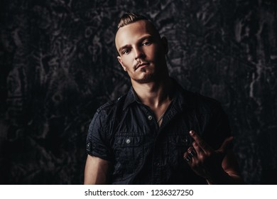 Portrait of a punk man   in black shirt on grunge background. Fashion, subculture. Studio shot.