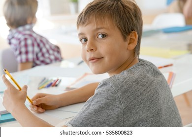 Portrait of pupil in school class taking notes during writing lesson