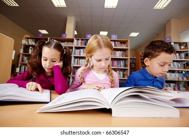 Portrait of pupils looking at pages of textbooks at reading lesson