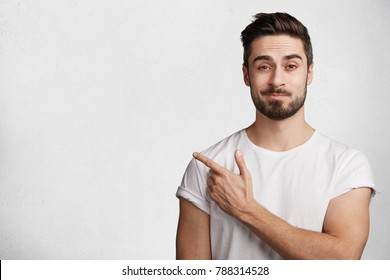 Portrait of puzzled bearded brunet male with beard and mustache wears casual white t shirt, points with fore finger at copy space for your promotional content. Advertising, facial expressions concept