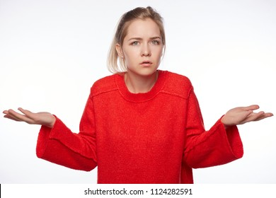 Portrait of puzzled intelligent female student wears red oversized sweater, feels awkward, shrugs shoulders with hesitation, sees no way out, not knowing material on exam isolated on white wall.