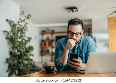 Portrait of a puzzled man looking at smart phone, sitting at table at home.