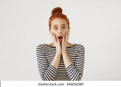 Portrait of puzzled woman with ginger hair bun feeling fear, keeping hands on cheeks, looking with great surprisment and amazement into camera, receiving bad news from her relatives or friends