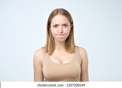 Portrait of puzzled woman looking with big opened eyes into camera biting her lips and having some doubts and uncertainty