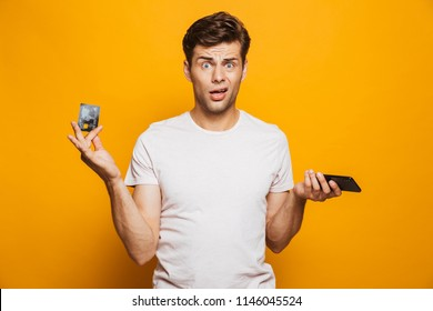 Portrait of a puzzled young man holding mobile phone and showing credit card isolated over yellow background