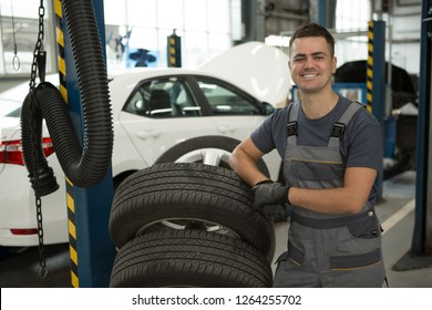 Portrait of qualified smiling worker of car service standing near tires, looking at camera and posing. Charming man in uniform and gloves enjoying his job at workshop. Concept of happiness.