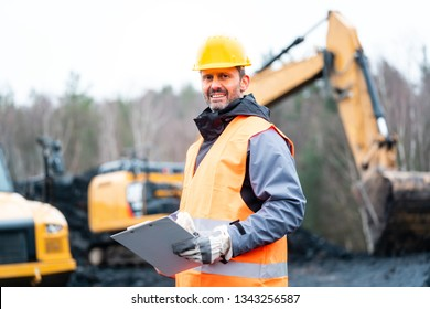 Portrait of a quarry worker standing in front of excavator smiling