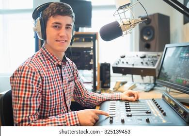 Portrait of radio host using sound mixer on table in studio