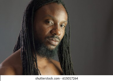 Portrait of a Rastafarian young male against a grey background