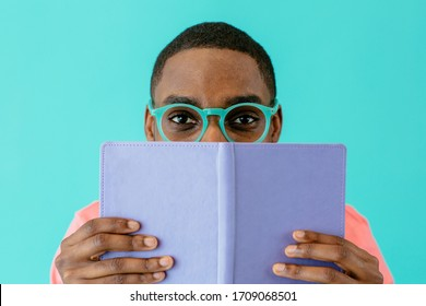 Portrait of a reader with glasses holding book and looking at camera, isolated on blue