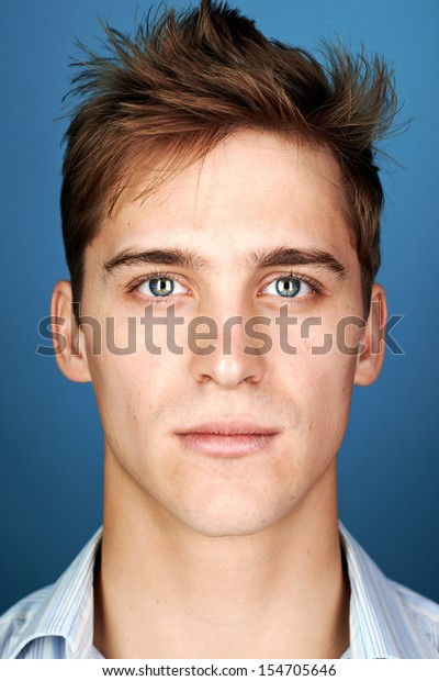 portrait of real man face looking at camera on blue background