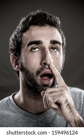Portrait of a real man with a finger in his nose