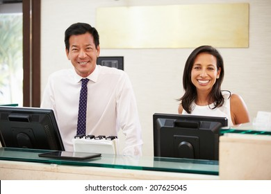 Portrait Of Reception Staff At Hotel Front Desk