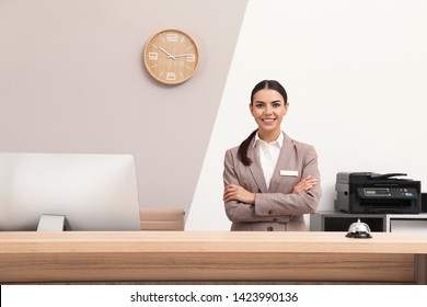 Portrait of receptionist at desk in modern hotel