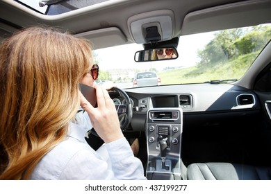 Portrait of reckless driver talking on mobile phone while driving on the road.