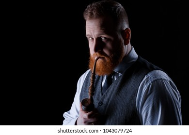 portrait of a red bearded man smoking a pipe on black background