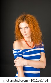 Portrait of red hair young woman on black background