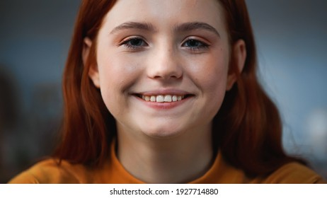 Portrait of red haired teenager smiling at camera