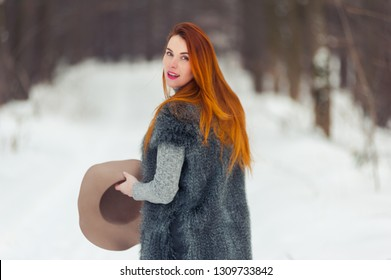 Portrait of red headed pregnant woman in snowy forest