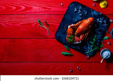 Portrait of a red lobster with a bouquet of parsley in a clove, small white snails grown on the lobsters shell, on a black stone tray on red wooden background, Valentines, Mothers day or Sorry Concept