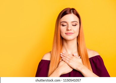 Portrait of red straight-haired attractive cute nice peaceful smiling young girl, touching chest with palms, closed eyes. Isolated over bright vivid yellow background