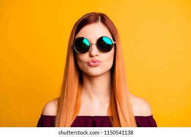 Portrait of red straight-haired attractive cute nice young girl, wearing sun glasses, blowing with puted lips. Isolated over bright vivid yellow background