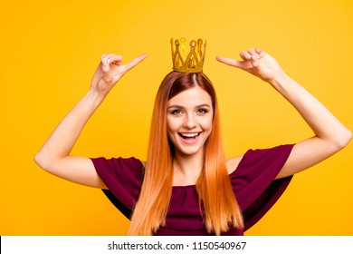Portrait of red straight-haired beautiful happy young girl, wearing diadem, pointing fingers showing golden shiny crown. Isolated over bright vivid yellow background