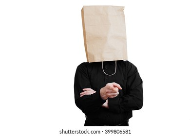 Portrait of a red-bearded, balding male brutal. White isolated background. Black shirt and pants. Paper bag over head. Dissatisfied with the situation  with arms folded, finger at viewer.