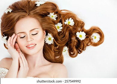 Portrait of red-haired beautiful and gentle girl with daisies in their hair lying on the floor with closed eyes , on a white background in Studio