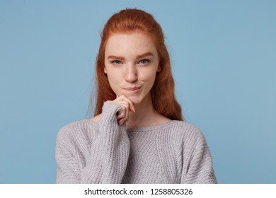 Portrait of a red-haired beautiful girl with a sly look, holds her hand near the chin bit her lip, she is up to something, preparing an venture, wants to organize an adventure.