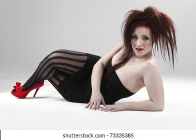 portrait of a red-haired female model on grey background